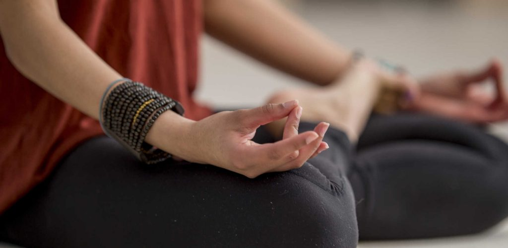 A teenage girl is indoors in a fitness studio. She is sitting cross-legged and meditating. The picture is focused on her lower body.